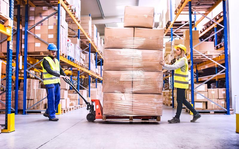 young-warehouse-workers-pulling-pallet-truck-boxes-109942380